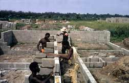 Workers build the exterior wall of a house in Zaire in   1975